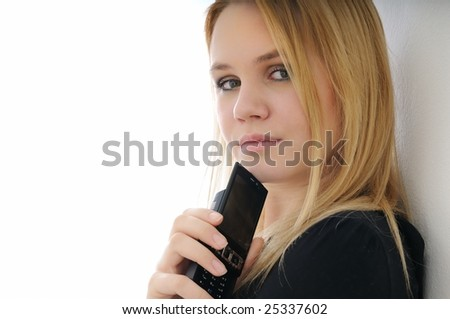 Blond thoughtful young woman holding mobile phone on white background
