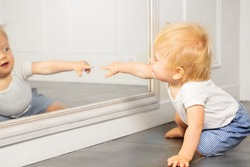 Blond toddler boy point to the mirror with finger