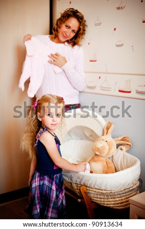 Blond toddler girl and her mother standing near baby cradle