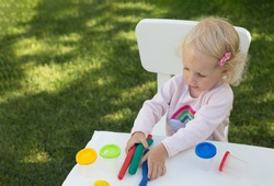 Blond toddler girl playing modeling clay in the garden in sunny summer day. She is sitting on white chair. Clay is bright and laying on white table.