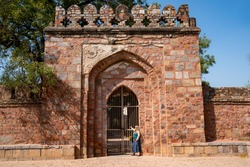 Blond tourist poses at the gate of Tomb of Sikandar Lodi, a ruler of the Lodi Dynasty in Lodi Gardens in New Delhi, India