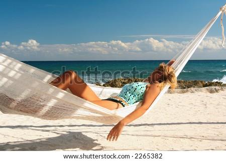 Blond woman asleep in a hammock. - stock photo