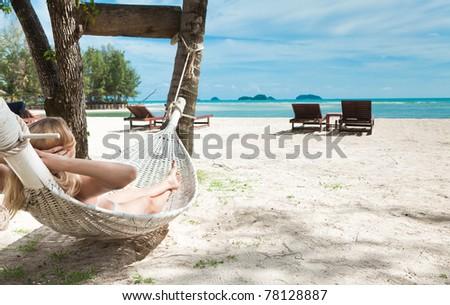 Blond woman asleep in a hammock.