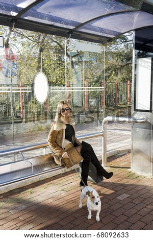 blond woman at the busstop holding a jack russel