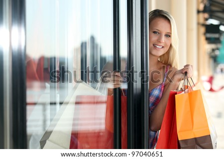 Blond woman coming out of clothes shop