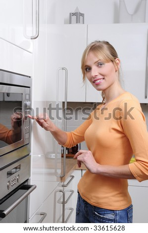 Blond woman cooking with a microwave in a modern kitchen