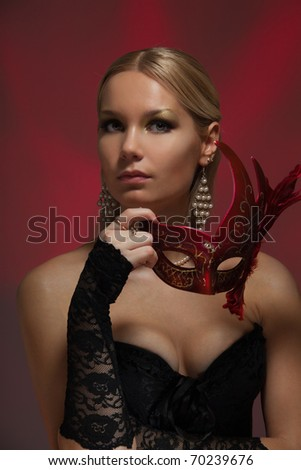 Blond woman corseted standing with disguise mask - stock photo