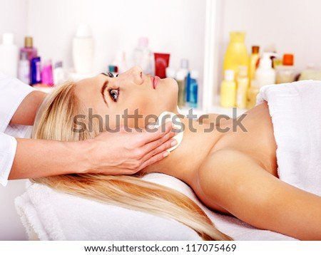 Blond woman getting head massage at spa.