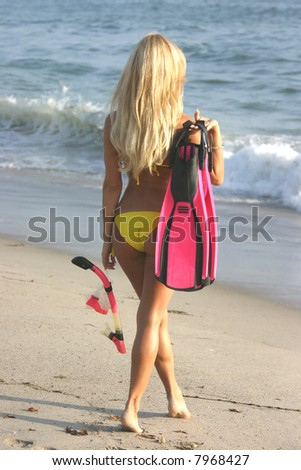 Blond woman going snorkeling walking towards the water.