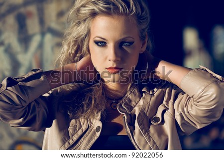 blond woman holding hands at the back wearing leather jacket inside ruins. Fashion photo