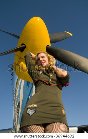 blond woman in an army outfit standing under the propeller of an aircraft