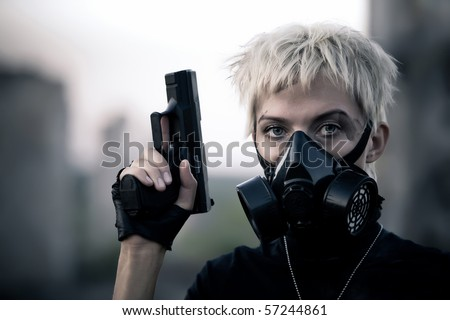 Blond woman in the gas mask with the pistol