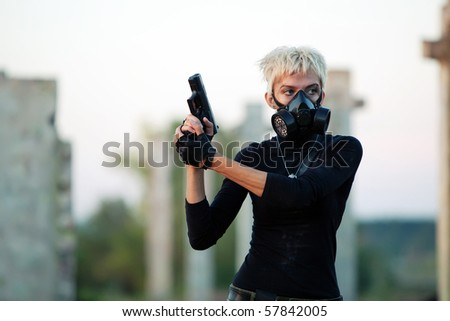 Blond woman in the gas mask with the pistol on the ruined background.