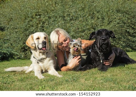 Blond woman is lying with three dogs at the lawn.