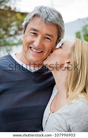 Blond woman kissing a cheerful middle aged man