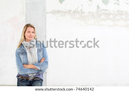 Blond woman leaning on concrete wall