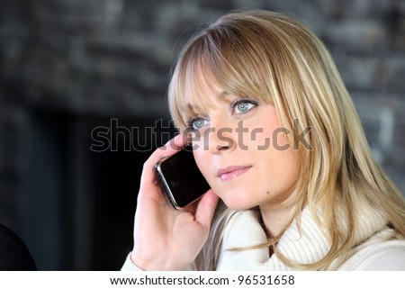 Blond woman making telephone call from home