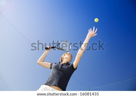 blond woman playing tennis about to hit the ball Copy space