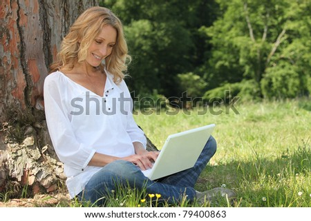 Blond woman sat by tree with laptop computer