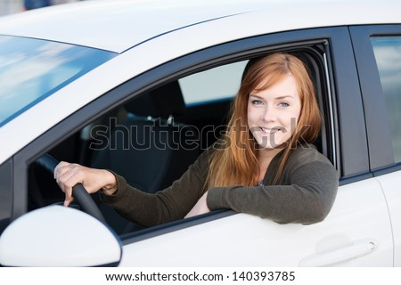 Blond woman sitting and driving in her car