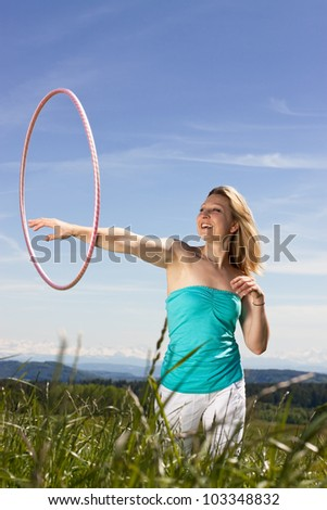 Blond woman standing on a lawn and plays with hula hoops