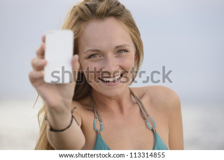 blond woman taking photo with cellphone on the beach