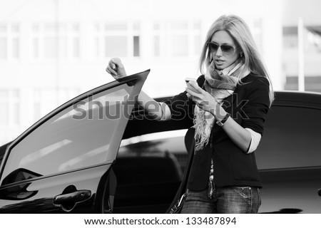 Blond woman with a car looking at mobile phone