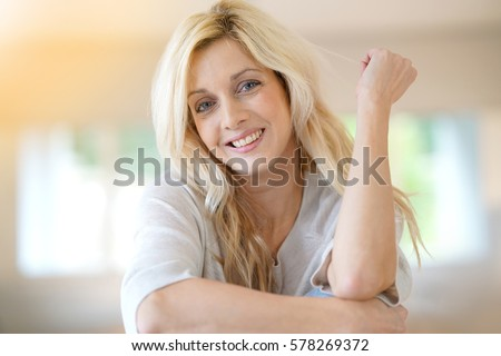 Blond woman with blue eyes sitting on table