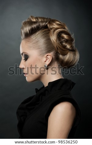 Blond woman with fashion hairstyle, eyes down.