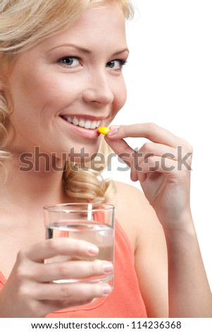 Blond woman with glass of water takes tablets, isolated on white
