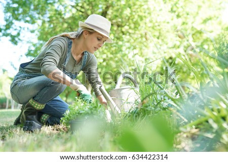 Blond woman with hat gardening