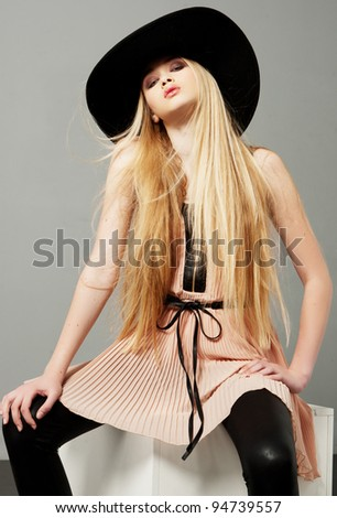 Blond woman  with long beautiful hair and smoky eyes in a hat. Studio