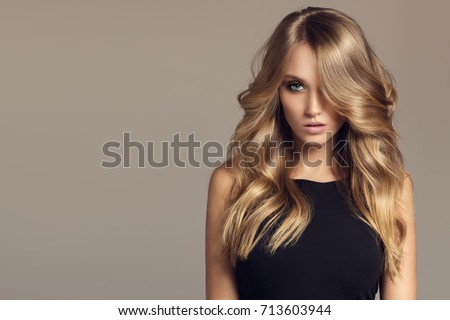 Blond woman with long curly beautiful hair.  #713603944
