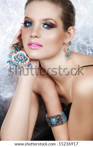 Blond woman with long false lashes holding pearl and blue stones golden jewelry with dreaming expression