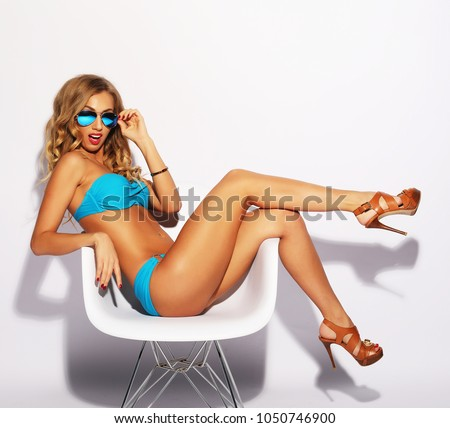 blond woman with long hair in blue underwear sitting on chair, over white background #1050746900