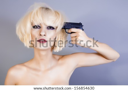 blond woman with pistol pointing on her head