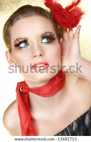 Blond woman with red rose in her hair and scarf listening with a hand next to her face, long feather false lashes