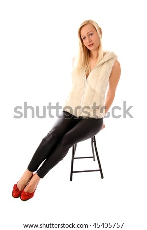 Blond woman with red shoes sitting on a chair