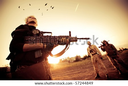 Blond woman with rifle is looking at ravens. Two rebels with Kalashnikov machine gun on the background.