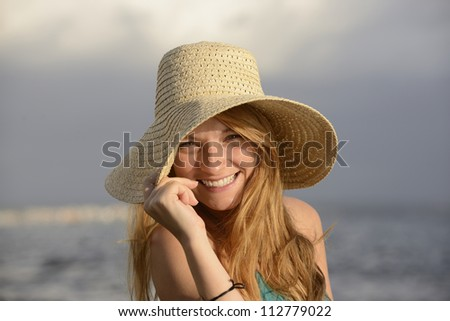 blond woman with sunhat on the beach laughing