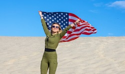 Blond woman with USA flag against blue sky and sandy beach proclaims America Independence Day.