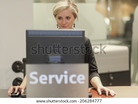 Blond woman working at help desk looking at the screen Freiburg Germany