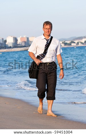 Blond , young businessman walks close to the sea