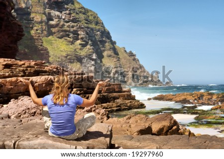 Blond young man meditates on rocks against sea-misty mountain background. Shot in Cape of Good Hope n Cape Point Nature Reserve, Table Mountain National Park, near Cape Town, South Africa.