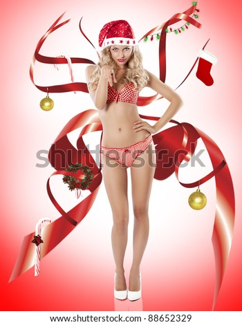 Blond young sexy girl in red lingerie posing like a pinup and wearing a santa claus hat and high heel looking like christmas spirit