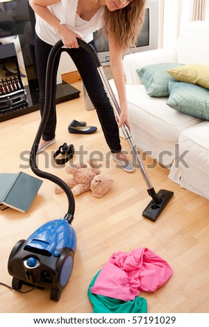 Blond young woman cleaning the living-room with a vacuum cleaner