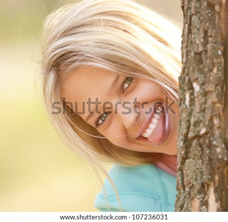 blond young woman looking out of the tree