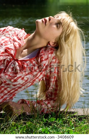blond young woman relaxing by the lake