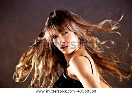 blond young woman with hair in motion, studio shot