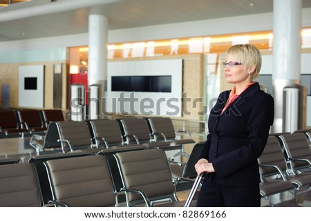 blonde adult businesswoman in black suit waiting for the departure of the plane in waiting room